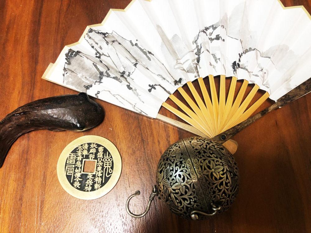 丸い銀製の香炉、銅製山鬼花銭、魚形文鎮、作家本人が描いた扇